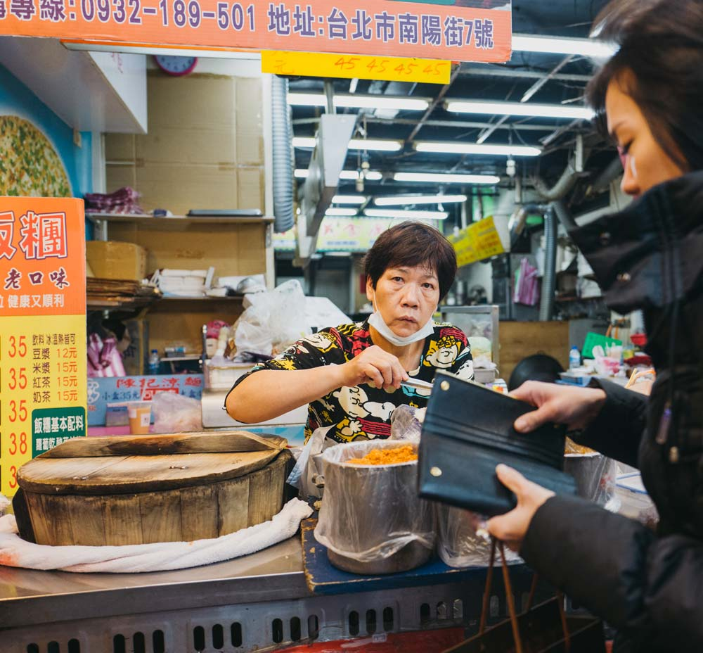 Woman in local market in Beijing china Cost of travel in china