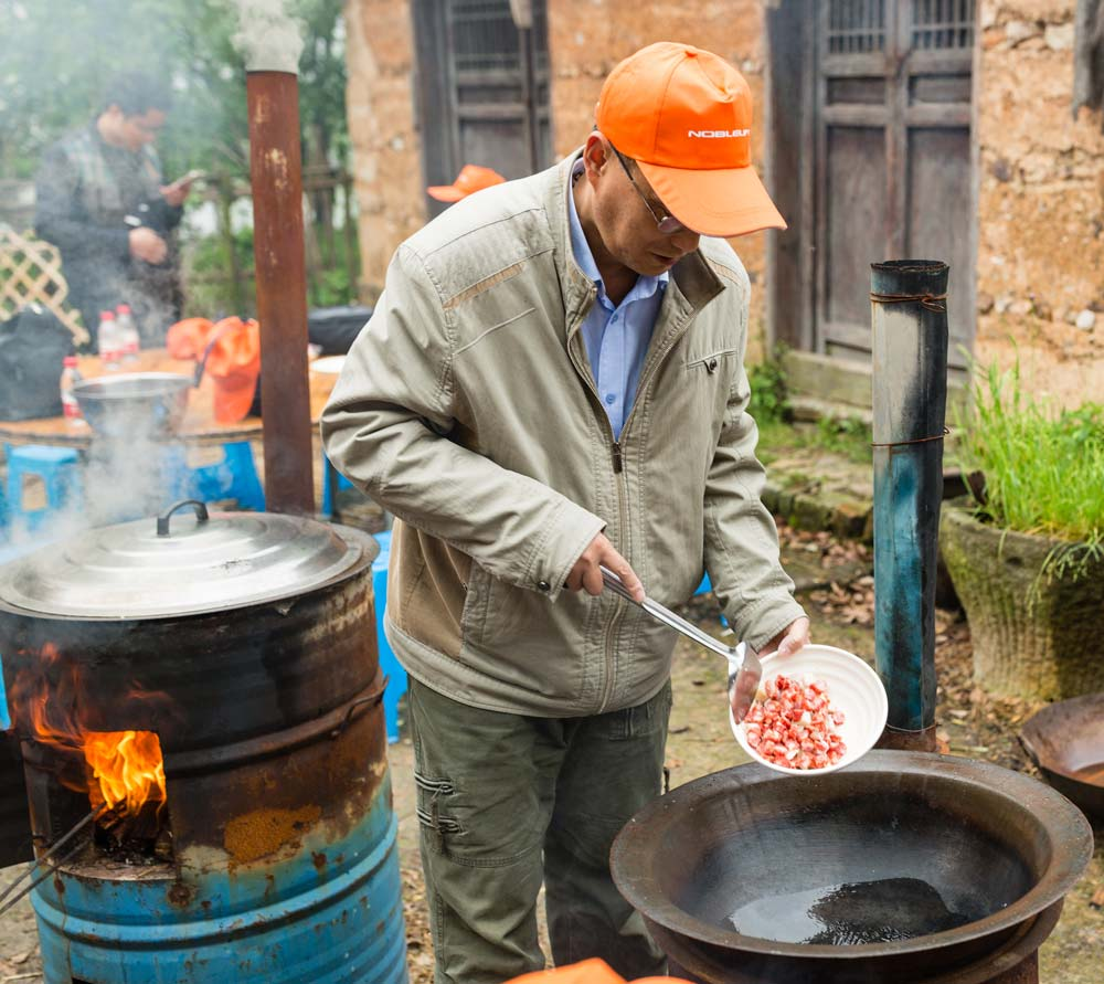 Local man cooking food in China Chinese market Cost of Travel in China