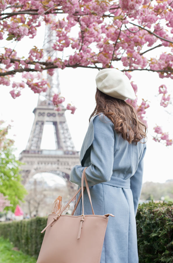 Woman looking at the Eiffel Tower under Cherry Blossom in Paris