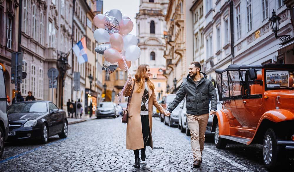 visit a city couple walking through Prague