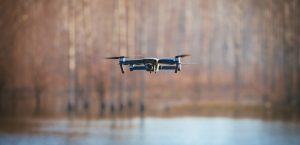 Drone flying over water in the woods