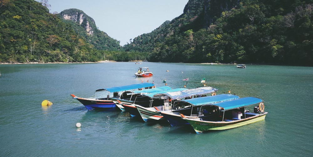 a row of local boats surrounded by karst mountains in Langkawi