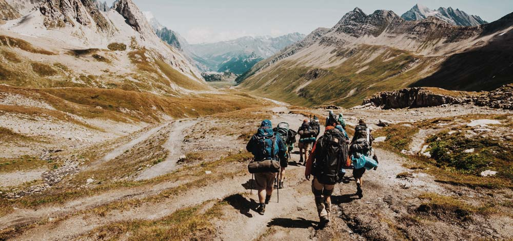 Group of travellers hiking through mountains cheapest ways to travel