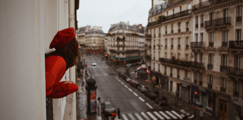 Woman looking out at street in Paris